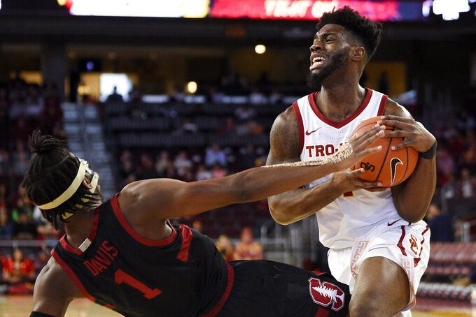 Southern California guard Daniel Utomi, right, fouls Stanford guard Daejon Davis while driving to the basket during the first half of an NCAA college basketball game in Los Angeles, Saturday, Jan. 18, 2020. (AP Photo/Kelvin Kuo)