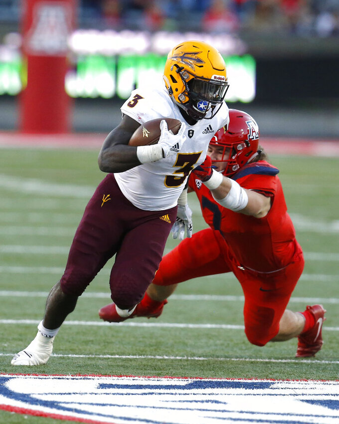 Arizona State running back Eno Benjamin (3) breaks the tackle of Arizona linebacker Colin Schooler in the second half during an NCAA college football game, Saturday, Nov. 24, 2018, in Tucson, Ariz. (AP Photo/Rick Scuteri)