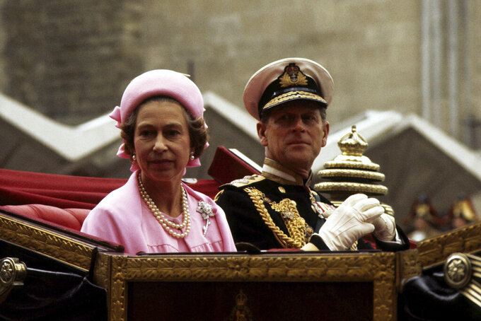 FILE - In this June 7, 1977 file photo, Britain's Queen Elizabeth II and Prince Philip travel in the open landau on the return processional drive to Buckingham Palace, London, after lunch at the Guildhall to celebrate the Silver Jubilee. Prince Philip, the irascible and tough-minded husband of Queen Elizabeth II who spent more than seven decades supporting his wife in a role that both defined and constricted his life, has died, Buckingham Palace said Friday, April 9, 2021. He was 99. (PA via AP, File)