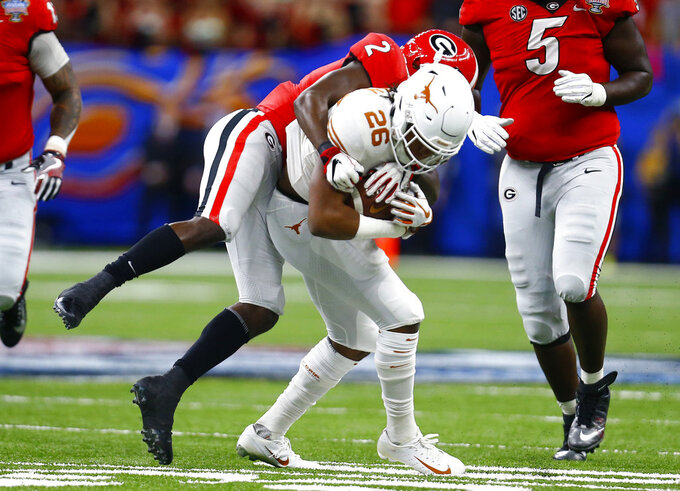 Texas running back Keaontay Ingram (26) is stopped by Georgia defensive back Richard LeCounte (2) during the first half of the Sugar Bowl NCAA college football game in New Orleans, Tuesday, Jan. 1, 2019. (AP Photo/Butch Dill)