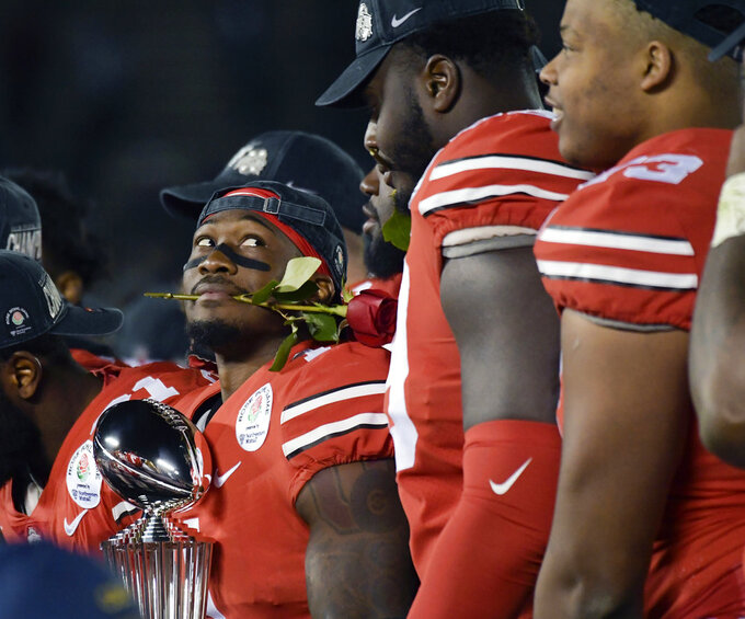 Ohio State wide receiver Johnnie Dixon holds the trophy after Ohio State's 28-23 win over Washington in the Rose Bowl NCAA college football game Tuesday, Jan. 1, 2019, in Pasadena, Calif. (AP Photo/Mark J. Terrill)