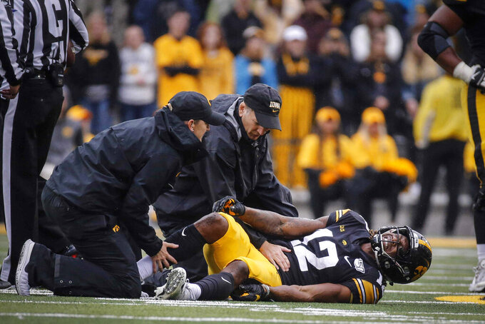 Members of Iowa's staff attend to junior wide receiver Brandon Smith after he injured his ankle in the fourth quarter of an NCAA college football game against Purdue, Saturday, Oct. 19, 2019, at Kinnick Stadium in Iowa City, Iowa. (Bryon Houlgrave/The Des Moines Register via AP)
