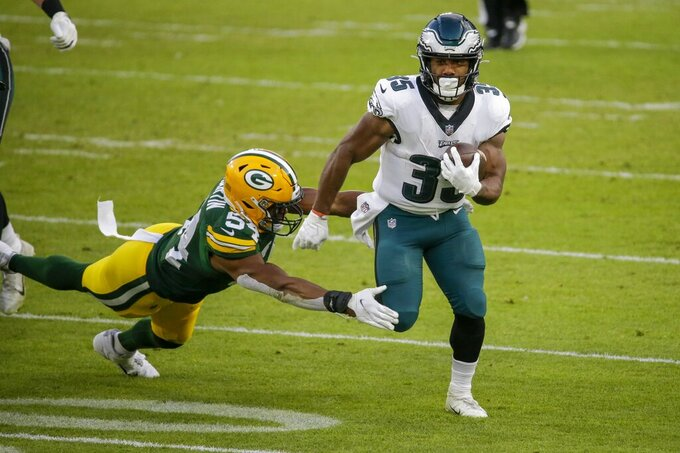 Philadelphia Eagles' Boston Scott runs past Green Bay Packers' Kamal Martin during the first half of an NFL football game Sunday, Dec. 6, 2020, in Green Bay, Wis. (AP Photo/Mike Roemer)