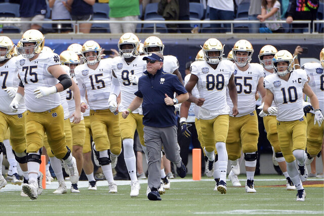 FILE - In this Dec. 28, 2019, file photo, Notre Dame head coach Brian Kelly, center, runs onto the field with his players before the Camping World Bowl NCAA college football game against Iowa State in Orlando, Fla. The Atlantic Coast Conference and Notre Dame are considering whether the Fighting Irish will give up their treasured football independence for the 2020 season play as a member of the league. (AP Photo/Phelan M. Ebenhack, File)