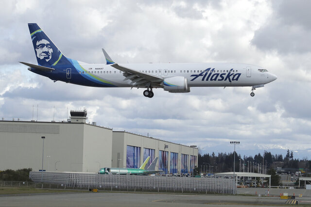 An Alaska Airlines Boeing 737-9 Max flies over Boeing's manufacturing facility in Everett, Wash., Monday, March 23, 2020, north of Seattle. All 737 Max planes remain grounded after two deadly crashes, but test and positioning flights continue to be made. Boeing announced Monday that it will be suspending operations and production at its Seattle area facilities due to the spread of the new coronavirus. (AP Photo/Ted S. Warren)