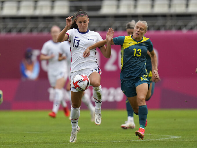 United States' Alex Morgan, left, and Australia's Tameka Yallop battle for the ball during a women's soccer match at the 2020 Summer Olympics, Tuesday, July 27, 2021, in Kashima, Japan. (AP Photo/Fernando Vergara)