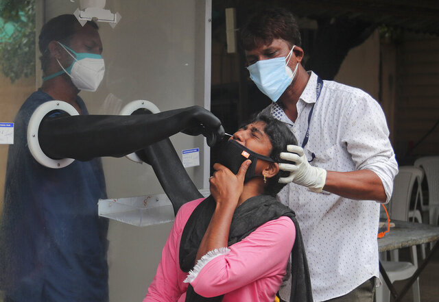 Health workers collect a nasal swab sample to test for COVID-19 in Hyderabad, India, Thursday, Sept. 17, 2020. As India's coronavirus confirmed cases jump by a record 97,894 cases in the past 24 hours, Prime Minister Narendra Modi's government faced a scathing opposition criticism in Parliament for its handling of the pandemic and a contracting economy leaving millions jobless on Thursday. (AP Photo/Mahesh Kumar A.)