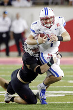 SMU quarterback Shane Buechele (7) is tackled by Houston defensive lineman Derek Parish, left, on a keeper during the second half of an NCAA college football game Thursday, Oct. 24, 2019, in Houston. (AP Photo/Michael Wyke)