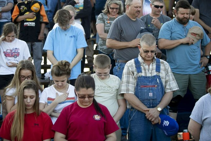 "In this Saturday, May 23, 2020 photo, race fans pray at the Ace Speedway on in the rural Alamance County community of Altamahaw near Elon, N.C. North Carolina Gov. Roy Cooper's administration has ordered closed a small stock-car track that's allowed large crowds to gather repeatedly for weekend races well above COVID-19 limits for mass gatherings. Cooper's health secretary says Ace Speedway in Alamance County is an ""imminent hazard"" for the virus' spread and can't reopen unless it creates a safety plan to keep fans away. (Robert Willett/The News & Observer via AP)"