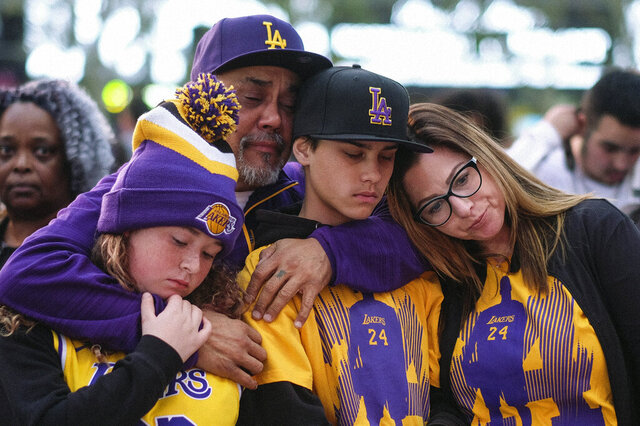 Fans pay respect at a memorial for Kobe Bryant near Staples Center Monday, Jan. 27, 2020, in Los Angeles. Bryant, the 18-time NBA All-Star who won five championships and became one of the greatest basketball players of his generation during a 20-year career with the Los Angeles Lakers, died in a helicopter crash Sunday. (AP Photo/Ringo H.W. Chiu)