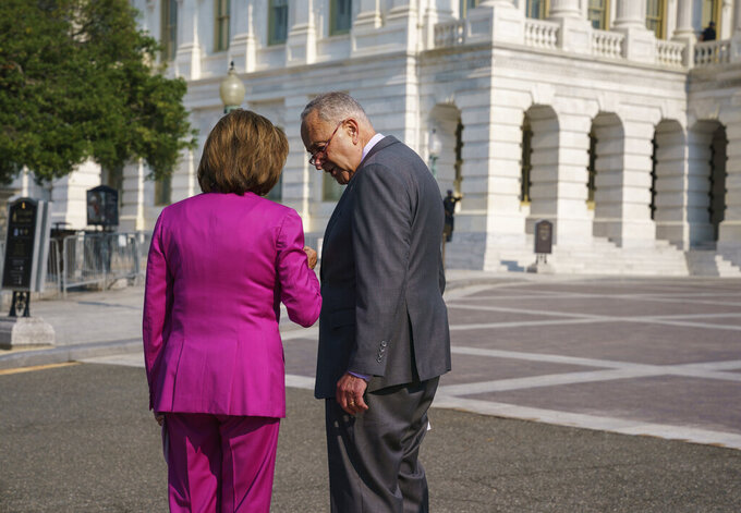Speaker of the House Nancy Pelosi, D-Calif., left, and Senate Majority Leader Chuck Schumer, D-N.Y., speak privately before an event to address the need to counter climate change in the US with transformational investments in clean jobs, at the Capitol in Washington, Wednesday, July 28, 2021. (AP Photo/J. Scott Applewhite)