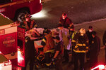 Emergency workers bring an injured person to an ambulance after a driver sped through a protest-related closure on the Interstate 5 freeway in Seattle, authorities said early Saturday, July 4, 2020. Dawit Kelete, 27, has been arrested and booked on two counts of vehicular assault. (James Anderson via AP)