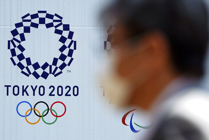 "FILE - In this April 2, 2020, file photo, a man wearing a face mask walks near the logo of the Tokyo 2020 Olympics, in Tokyo. Tokyo organizers said Tuesday, April 14, 2020 they have no ""B Plan"" for again rescheduling the Olympics, which were postponed until next year by the virus pandemic. They say they are going forward under the assumption the Olympics will open on July 23, 2021. (AP Photo/Eugene Hoshiko, File)"