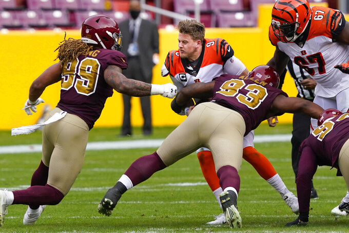Cincinnati Bengals quarterback Joe Burrow (9) looses his helmet as he is tackled by Washington Football Team defensive tackle Jonathan Allen (93) during the first half of an NFL football game, Sunday, Nov. 22, 2020, in Landover. (AP Photo/Susan Walsh)