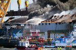 Smoke pours out of the hull of the Golden Ray cargo ship as firefighters hose down the remains of the overturned vessel, Friday, May 14, 2021, in Brunswick, Ga. The Golden Ray had roughly 4,200 vehicles in its cargo decks when it capsized off St. Simons Island on Sept. 8, 2019. (AP Photo/Stephen B. Morton)
