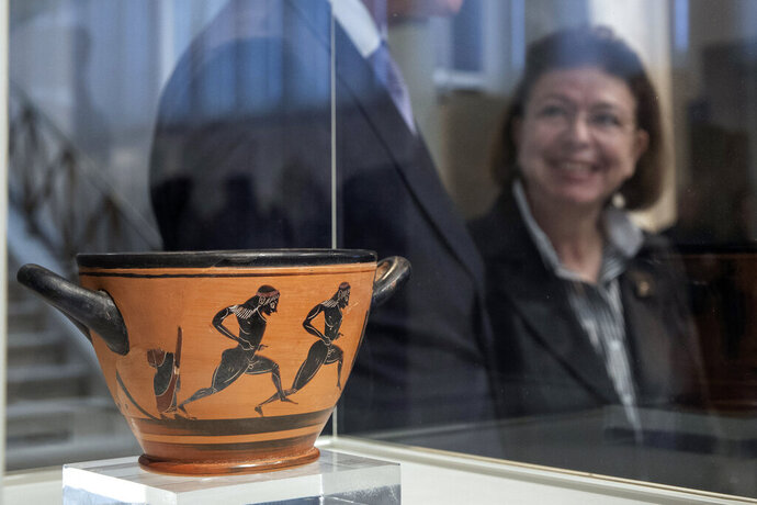Greek Culture Minister Lina Mendoni stands behind an ancient Greek drinking cup decorated with runners, which was one of the awards presented to Spyros Louis, the Greek winner of the Marathon in the 1896 first modern Olympic Games, at the National Archaeological Museum in Athens on Wednesday, Nov. 13, 2019. Greece's Culture Ministry said Wednesday the ancient vase has been returned to Athens by the University of Muenster in Germany where it had ended up.(AP Photo/Petros Giannakouris)