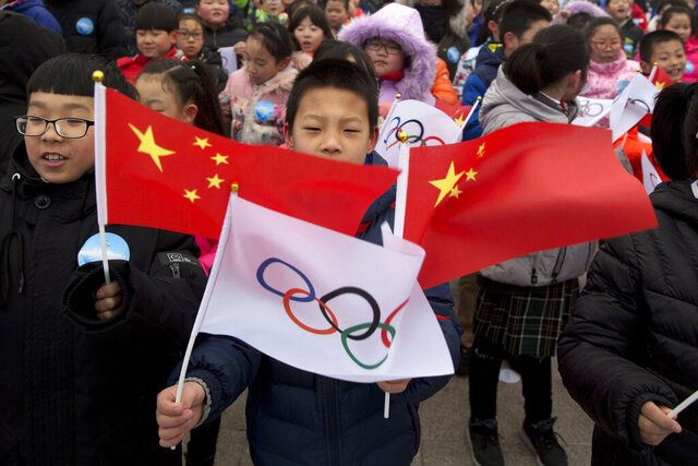 FILE - In this Feb. 27, 2018, file photo, a child waves a Chinese national flag and an Olympic flag during a ceremony to mark the arrival of the Olympic flag and start of the flag tour for the Winter Olympic Games Beijing 2022 at a section of the Great Wall of China on the outskirts of Beijing. Uncertainty surrounds how the postponed Tokyo Olympics will be held next year in the midst of the coronavirus. The same questions permeate three mega-events that will be staged in China within a year after the Tokyo Games close. (AP Photo/Ng Han Guan, File)