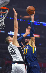 Utah Jazz center Rudy Gobert, right, shoots as Los Angeles Clippers center Ivica Zubac defends during the first half of an NBA basketball game Saturday, Dec. 28, 2019, in Los Angeles. (AP Photo/Mark J. Terrill)