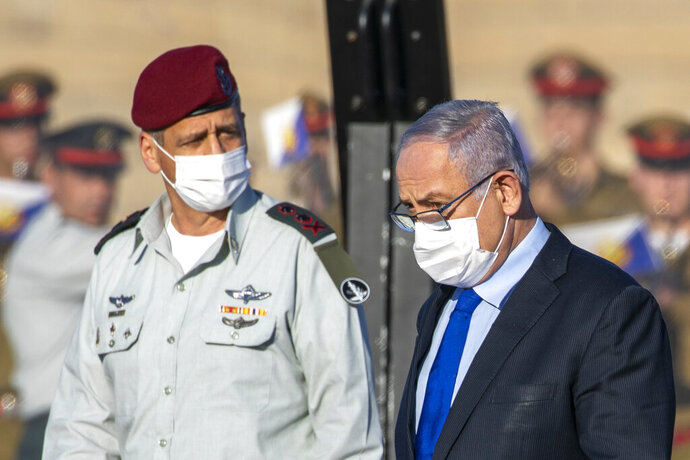 Israeli Prime Minister Benjamin Netanyahu, right, and Israeli Chief Aviv Kochavi, wearing face masks attend a graduation ceremony for new pilots in Hatzerim air force base near the southern Israeli city of Beersheba, Israel, Thursday, June 25, 2020. (AP Photo/Ariel Schalit, Pool)