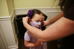 Rachel Adamus, right, helps her daughter Neva, 5, put on her mask before her first day of kindergarten on Monday, Aug. 3, 2020, in Dallas, Ga. Neighboring states arrived at differing conclusions on who's in charge of the reopening of schools. The differences in philosophy underscore some of the difficulties facing states as they grapple with how to proceed amid growing coronavirus infections in numerous states.(AP Photo/Brynn Anderson)
