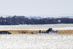 Law enforcement surveys the scene of a plane crash on Monday, Dec. 2, 2019, in Chamberlain, S.D. Nine people were killed and three people were injured when a plane crashed shortly after taking off on Saturday, Nov. 30, 2019. (Abigail Dollins/The Argus Leader via AP)