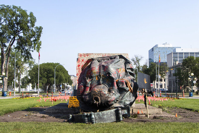 A headless statue of Queen Victoria is seen overturned and vandalized at the provincial legislature in Winnipeg, Friday, July 2, 2021. Her statue and a statue of Queen Elizabeth II were toppled on Canada Day during demonstrations concerning Indigenous children who died at residential schools.  (Kelly Geraldine Malone/The Canadian Press via AP)