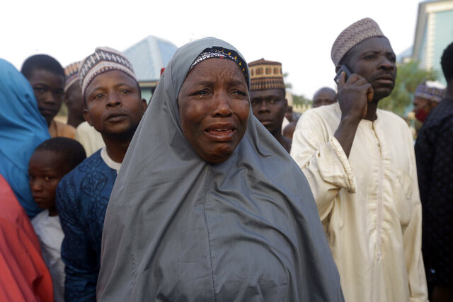 A family member of a freed schoolboy cries as she waits for a reunion with her son in Katsina Nigeria Friday Dec. 18, 2020. More than 300 schoolboys kidnapped last week in an attack on their school in northwest Nigeria have arrived in the capital of Katsina state to celebrate their release. The boys were abducted one week ago from the all-boys Government Science Secondary School in Kankara in Katsina state village. (AP Photo/Sunday Alamba)