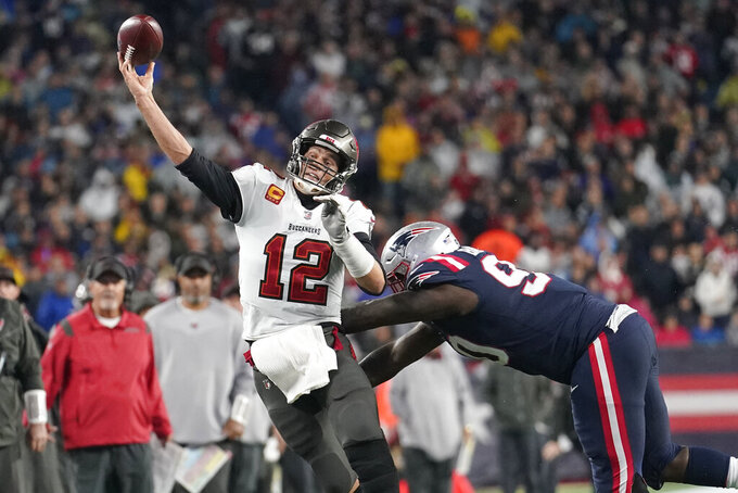 Tampa Bay Buccaneers quarterback Tom Brady (12) throws while pressured by New England Patriots defensive tackle Christian Barmore (90) during the second half of an NFL football game, Sunday, Oct. 3, 2021, in Foxborough, Mass. (AP Photo/Steven Senne)