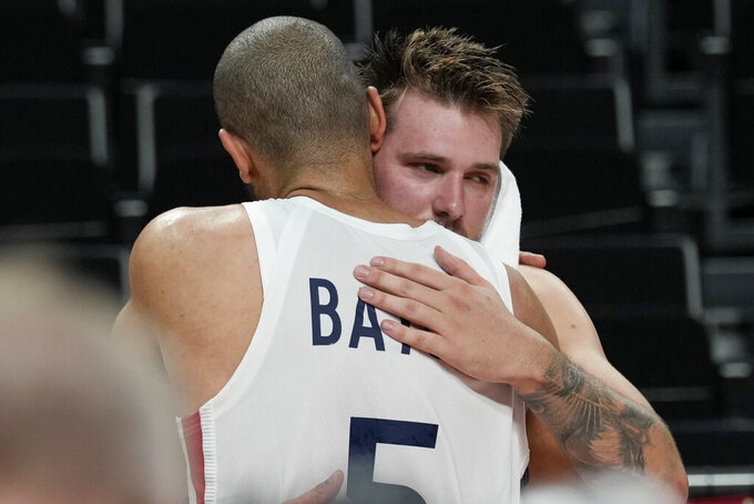 Slovenia's Luka Doncic, right, is hugged by France's Nicolas Batum (5) after their men's basketball semifinal round game at the 2020 Summer Olympics, Thursday, Aug. 5, 2021, in Saitama, Japan. France won 90-89. (AP Photo/Eric Gay)