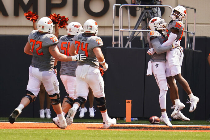 Oklahoma State wide receiver Jaden Bray (85) celebrates his touchdown with teammate Rashod Owens (10) in the first half of an NCAA college football game against Tulsa, Saturday, Sept. 11, 2021, in Stillwater, Okla. (AP Photo/Sue Ogrocki)