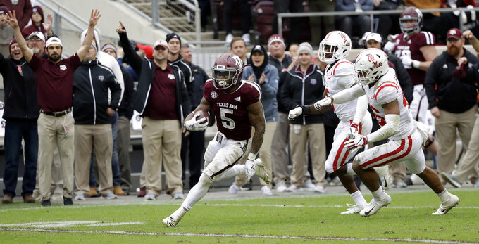 Texas A&M running back Trayveon Williams (5) breaks away from Mississippi defenders to score a touchdown during the fourth quarter of an NCAA college football game Saturday, Nov. 10, 2018, in College Station, Texas. Texas A&M won 38-24. (AP Photo/David J. Phillip)