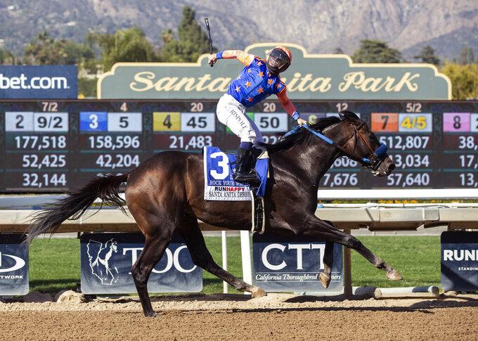 In a photo provided by Benoit Photo, Rock Your World and jockey Umberto Rispoli win the Grade I $750,000 Santa Anita Derby Saturday, April 3, 2021 at Santa Anita Park in Arcadia, Calif. (Benoit Photo via AP)