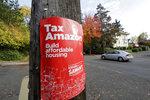 FILE - In this Oct. 23, 2019, file photo, a campaign poster for Seattle City Council incumbent candidate Kshama Sawant is posted outside her campaign headquarters in Seattle. The Seattle City Council on Monday, Jan. 13, 2020, unanimously passed a measure to reel in political spending by