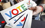 FILE - In this Monday, Nov. 5, 2018 file photo, bumper stickers are handed out during a rally in support of the 2026 Winter Olympic bid in Calgary, Alberta, Monday, Nov. 5, 2018.  Two candidates have stayed on the ballot to be held on Monday, June 24, 2019 to pick the 2026 Winter Olympics host. The IOC worked hard to help keep the Italian and Swedish candidates in the contest, giving both extra time to get their government's backing amid taxpayer concerns that Olympic hosting is an expensive luxury. Olympic officials hope the 2026 contest can shape a more efficient type of bidding and hosting. (Jeff McIntosh/The Canadian Press via AP, File)