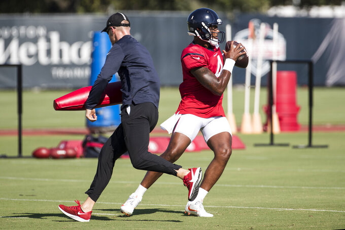 Houston Texans quarterback Deshaun Watson (4) steps up as he dodges assistant quarterbacks coach T.J. Yates during an NFL training camp football practice Thursday, Aug. 20, 2020, in Houston. (Brett Coomer/Houston Chronicle via AP, Pool)