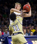 Notre Dame's Dane Goodwin (23) has the ball knocked away by Georgia Tech's Bubba Parham (11) during the first half of an NCAA college basketball game Saturday, Feb. 1, 2020, in South Bend, Ind. (AP Photo/Robert Franklin)