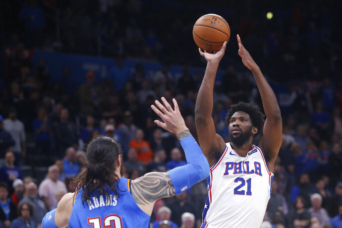 Philadelphia 76ers center Joel Embiid (21) shoots over Oklahoma City Thunder center Steven Adams, left, in the first half of an NBA basketball game Friday, Nov. 15, 2019, in Oklahoma City. (AP Photo/Sue Ogrocki)