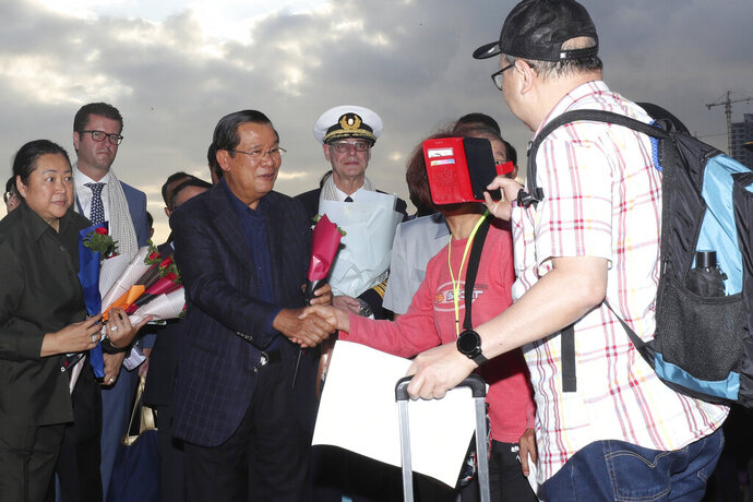 Cambodia's Prime Minister Hun Sen, center left, greets passengers after they disembarked from the MS Westerdam, owned by Holland America Line, at the port of Sihanoukville, Cambodia, Friday, Feb. 14, 2020. Hundreds of cruise ship passengers long stranded at sea by virus fears cheered as they finally disembarked Friday and were welcomed to Cambodia. (AP Photo/Heng Sinith)