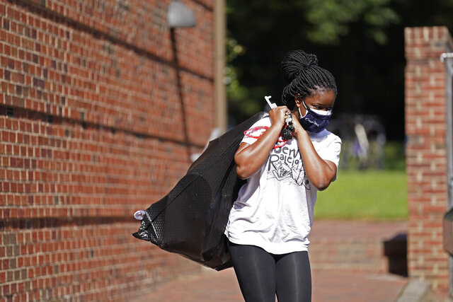 Oyeronke Popoola, a 17-year-old freshman from Raleigh, carries some of her belongings as she and other students leave campus following a cluster of COVID-19 cases at The University of North Carolina in Chapel Hill, N.C., Tuesday, Aug. 18, 2020. The university announced that it would cancel all in-person undergraduate learning starting on Wednesday. (AP Photo/Gerry Broome)