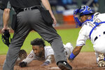 Detroit Tigers' Niko Goodrum beats the tag by Kansas City Royals catcher Salvador Perez to score on a sacrifice fly by Eric Haase during the seventh inning of a baseball game Friday, Sept. 25, 2020, in Kansas City, Mo. (AP Photo/Charlie Riedel)