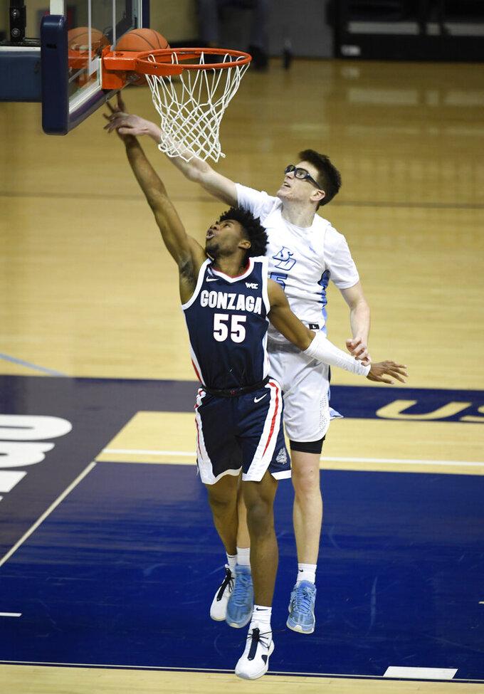 Gonzaga guard Dominick Harris (55) shoots past San Diego guard Finn Sullivan (5) during the second half of an NCAA college basketball game Thursday, Jan. 28, 2021, in San Diego. (AP Photo/Denis Poroy)