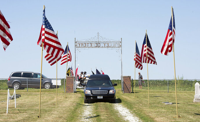 In this Thursday, Aug. 9, 2018 photo, the hearse carrying World War II Flight Officer Richard Lane's casket arrives for burial services at Filley Cemetery in Filley, Neb. The remains of a World War II pilot were finally buried with full military honors in his home state of Nebraska after 73 years in foreign soil. Lane, who died in combat in 1944, had been buried in a military cemetery in Belgium in a grave marked