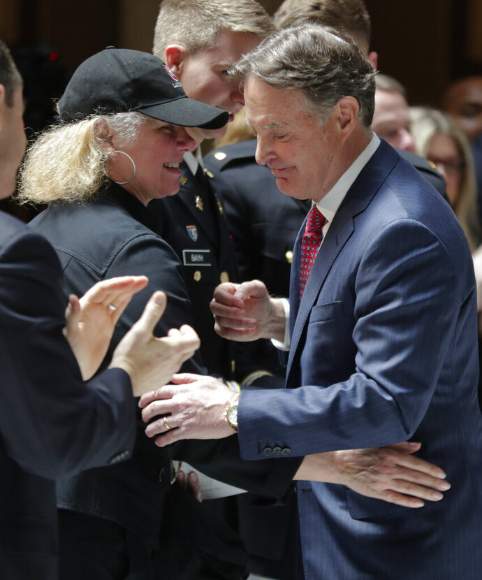 Former Indiana Governor and Sen. Evan Bayh hugs his wife, Susan, after he delivered remarks about his father as hundreds of mourners gathered at a memorial service honoring former U.S. Sen. Birch Bayh at the Indiana Statehouse in Indianapolis, Wednesday, May 1, 2019. Bayh died in March at the age of 91. The Democrat represented Indiana in the Senate for 18 years until he lost his 1980 re-election bid.(AP Photo/Michael Conroy)