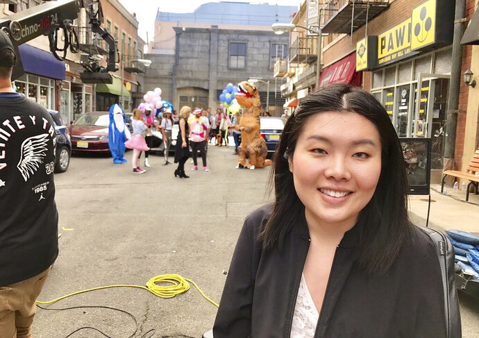 In this image provided by Kaitlyn Yang, Yang poses for a photo on the set of