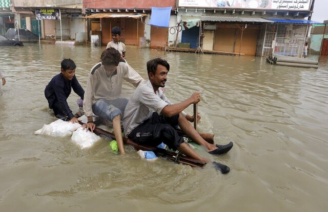 Local residents float through flooded area caused by heavy monsoon rains, in Karachi, Pakistan, Friday, Aug. 28, 2020. Heavy rains hit Pakistan's financial capital Karachi for a fifth straight night, bringing more flooding and killing some more people, officials said, as rescuers evacuated people from flooded neighborhoods. (AP Photo/Fareed Khan)