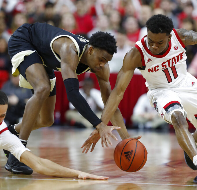 North Carolina State's Markell Johnson, right, and Wake Forest's Isaiah Mucius (1) go after the ball during the first half of an NCAA college basketball game in Raleigh, N.C., Friday, March 6, 2020. (Ethan Hyman/The News & Observer via AP)
