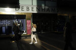 A woman wearing a face mask walks past the Debenhams flagship department store on Oxford Street, during England's second coronavirus lockdown in London, Tuesday, Dec. 1, 2020. In another dark day for the British retailing industry, Debenhams said Tuesday it will start liquidating its business after a potential buyer of the company pulled out, a move that looks like it will cost 12,000 workers their jobs. (AP Photo/Matt Dunham)