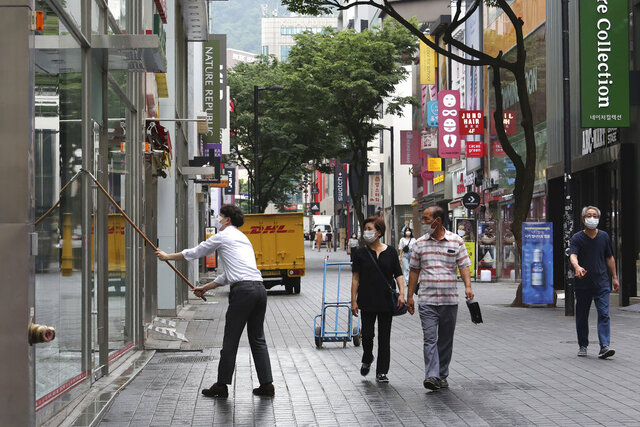 An employee wearing a face mask to help protect against the spread of the new coronavirus cleans the widows of his shoe store at a shopping street in Seoul, South Korea, Friday, June 12, 2020. (AP Photo/Ahn Young-joon)