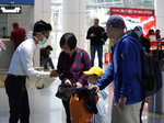 Health officials check passengers at the Kuala Lumpur International Airport in Sepang, Malaysia, Tuesday, Jan. 21, 2020. Countries both in the Asia-Pacific and elsewhere have initiated body temperature checks at airports, railway stations and along highways in hopes of catching those at risk of carrying a new coronavirus that has sickened more than 200 people in China. (AP Photo/Vincent Thian)