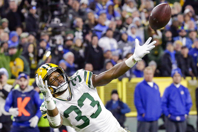 Green Bay Packers running back Aaron Jones tries to pull down a pass during the first half of an NFL football game against the Detroit Lions, Monday, Oct. 14, 2019, in Green Bay, Wis. (AP Photo/Mike Roemer)